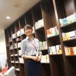 大きな本棚の前で笑顔の河本真紀子